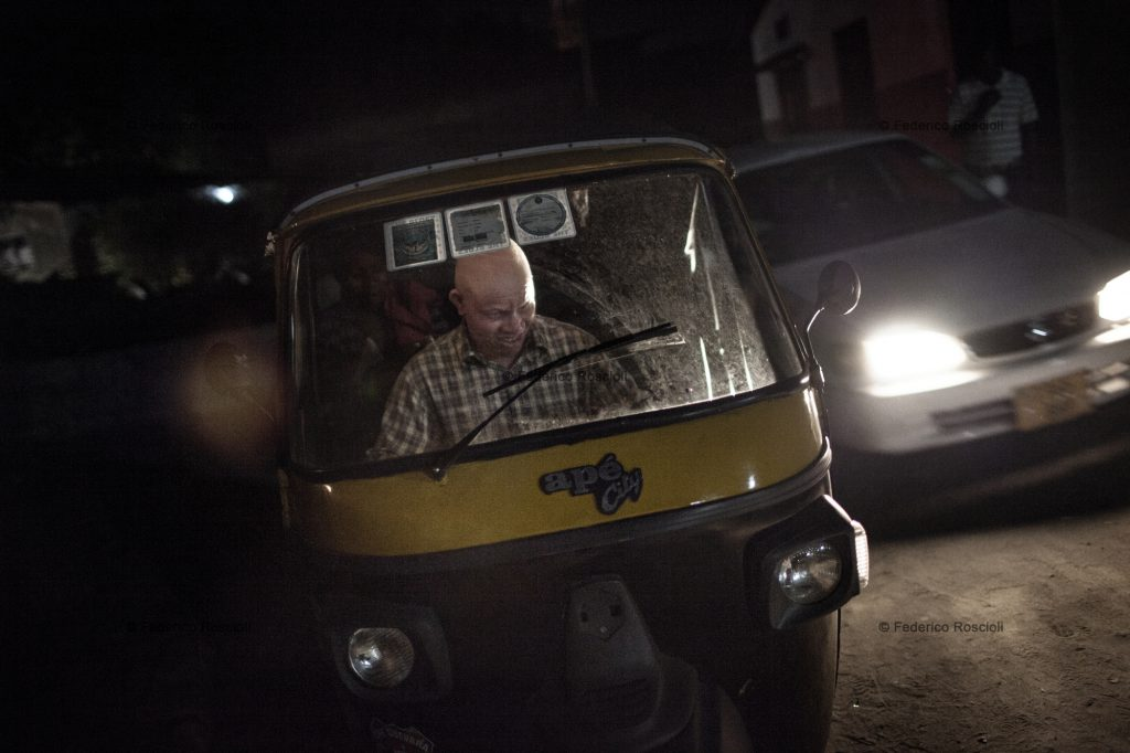 Dar es Salaam, Tanzania, July 29, 2014 - Redman driving his bajaj in Dar es Salaam, Tanzania. Despite albinism, he has been a driver for 9 years, the last 3 on a bajaj. A Bajaj is a three-wheel taxi, perfect to move in Dar traffic. Being covered on the top, it is also a shield from the sun for an albino. Redman also has to fight against discrimination to be able to work. He has to pay a person to pick up the bajaj from the owner every day, as the owner does not want albino drivers, not trusting their sight.
