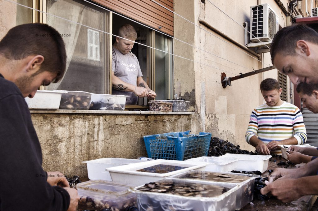 Taranto, Italy, September 26, 2013. Armando and his friends cleaning mussels in Cittˆ Vecchia. Armando works form the window of is house because is under house arrest. In 2012, due to high levels of dioxin and Pcb, 20 tons of mussels were destroyed, half of the yearly production. Actually it is forbidden to cultivate mussels in Mar Piccolo. Doing so, all the environmental characteristics that gave the unicity to the Tarantinian mussels are lost. ### Taranto, Italia, 26 Settembre 2013. Armando e i suoi amici puliscono le cozze nella Cittˆ Vecchia. Armando  agli arresti domiciliari, per questo motivo lavora dalla finestra di casa. Nel 2012, a causa dellÕalta concentrazione di diossina e Pcb rilevata dalla Asl di Taranto, sono state fatte distruggere circa 20 mila tonnellate di cozze (metˆ della produzione complessiva). Attualmente  vietata la coltura dei mitili nel primo seno del Mar Piccolo. In questo modo si perdono quelle caratteristiche ambientali che fornivano alle cozze e ostriche tarantine la loro unicitˆ.