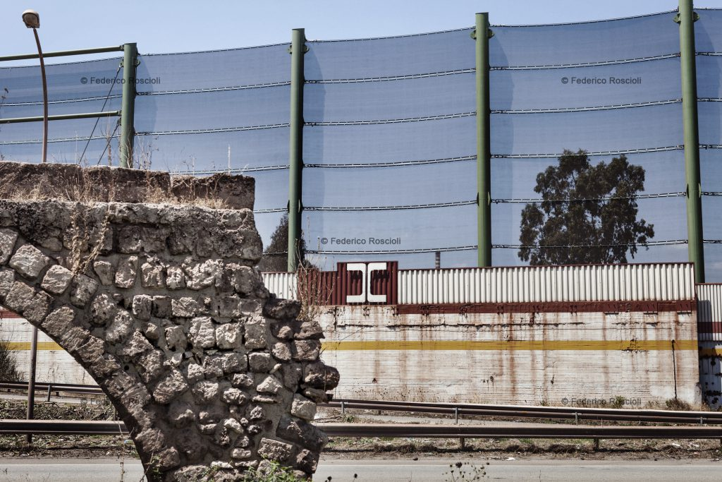 Taranto, Italy, August 1, 2013. Enclosure of Ilva factory in Taranto. The fence   over the wall was built in 2012 to protect the near neighborhood of Tamburi from the mineral dust coming from the implant. In foreground, the remains of the ancient Triglio aqueduct, belonging to Roman's eve. The Tamburi (literally ÒdrumsÓ) neighborhood is called so due to the sound made by the water dropping from the aqueduct. ### Taranto, Italia, 1 Agosto 2013. Recinzione dello stabilimento Ilva di Taranto. La rete sopra alle mura  stata costruita nel 2012 come previsto dallÕAia (Autorizzazione Integrata Ambientale rilasciata dal Ministero dellÕAmbiente) per difendere l'adiacente quartiere dei Tamburi dalla diffusione delle polveri di minerali provenienti dallÕimpianto. In primo piano, i resti dell'acquedotto del Triglio, di epoca romana. Tamburi deve il proprio nome al rumore delle gocce di acqua che cadevano dallÕacquedotto, simile al suono delle percussioni.