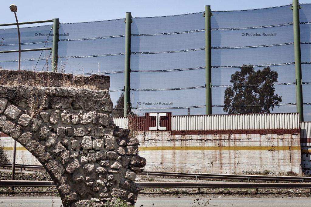Taranto, Italy, August 1, 2013. Enclosure of Ilva factory in Taranto. The fence   over the wall was built in 2012 to protect the near neighborhood of Tamburi from the mineral dust coming from the implant. In foreground, the remains of the ancient Triglio aqueduct, belonging to Roman's eve. The Tamburi (literally ÒdrumsÓ) neighborhood is called so due to the sound made by the water dropping from the aqueduct. ### Taranto, Italia, 1 Agosto 2013. Recinzione dello stabilimento Ilva di Taranto. La rete sopra alle mura  stata costruita nel 2012 come previsto dallÕAia (Autorizzazione Integrata Ambientale rilasciata dal Ministero dellÕAmbiente) per difendere l'adiacente quartiere dei Tamburi dalla diffusione delle polveri di minerali provenienti dallÕimpianto. In primo piano, i resti dell'acquedotto del Triglio, di epoca romana. Tamburi deve il proprio nome al rumore delle gocce di acqua che cadevano dallÕacquedotto, simile al suono delle percussioni.