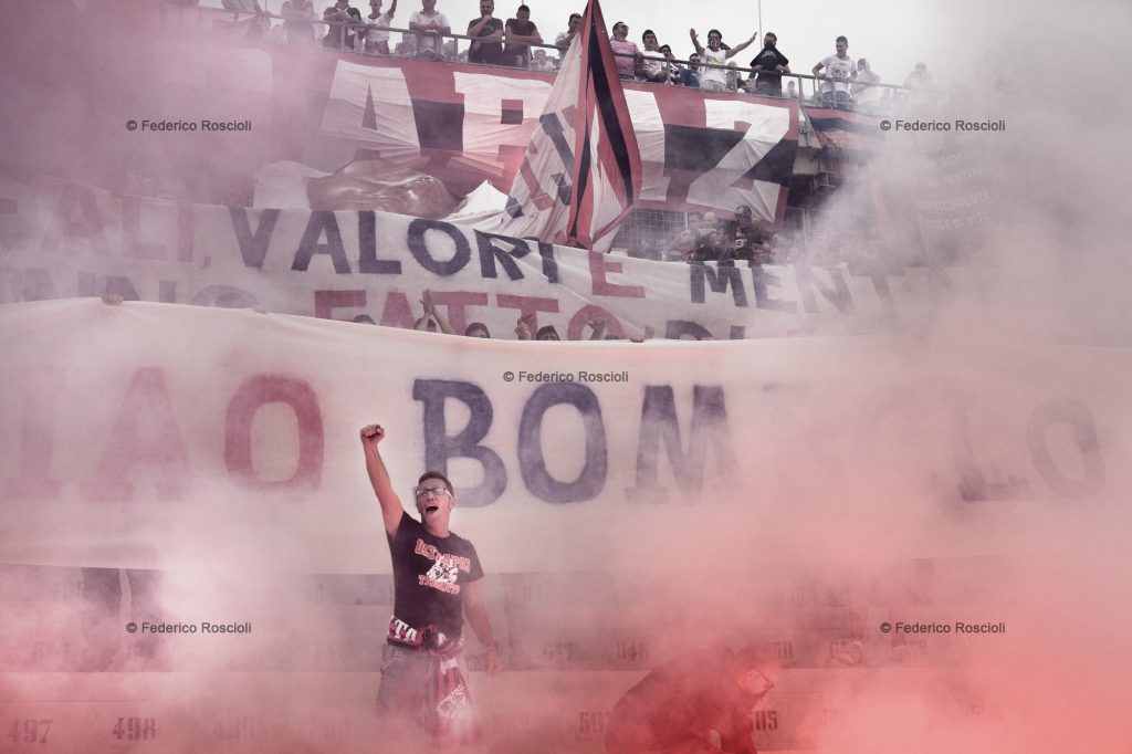 Taranto, Italy, September 29, 2013. Supporters remembering one of their buddy passed away with smoke and banners in Erasmo Iacovone Stadium in Taranto. Taranto Calcio plays actually in 4th division, due to the failure of the society, anyway it has an average attendance of around 2500 supporters. In the past taranto played 32 seasons in second division. The ÒcurvaÓ, in 1977 and 2001, was awarded as the best of Italy. ### Taranto, Italia, 29 Settembre 2013. I tifosi della curva nord ricordano la scomparsa di un loro compagno con una coreografia di striscioni e fumogeni allo stadio Erasmo Iacovone di Taranto. Il Taranto Calcio  attualmente in serie D a seguito dellÕennesimo fallimento della societˆ, ma conta una presenza media di circa 2500 tifosi. Nel passato ha disputato ben 32 stagioni in serie B. La curva, nel 1977 e nel 2001,  stata premiata come Miglior curva italiana.